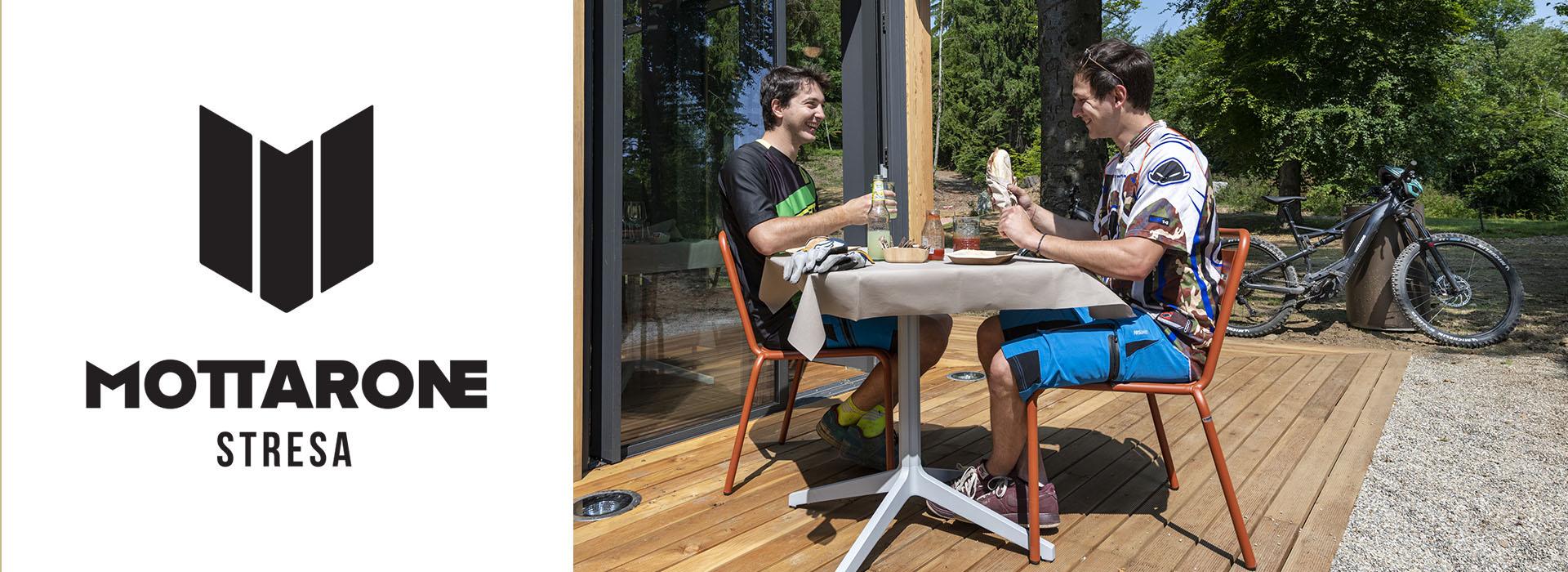 ragazzi seduti al tavolo che mangiano un panino